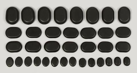Zawartość zestawu 36 kamieni bazaltowych do masażu.
